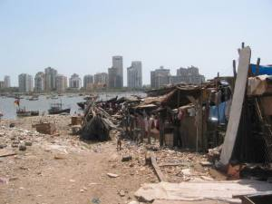 A slum on the banks of Bandra Creek, with highrises in the distance.